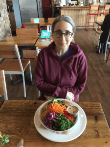 A person sitting at a table in front of a plate of food